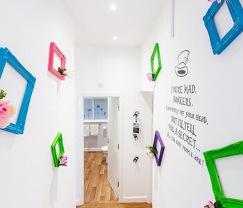 A hallway with colourful frames and writing on the wall