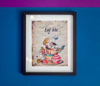 A framed photo with 'Eat Me' on a wall at the Mad Hatter's Tea Room
